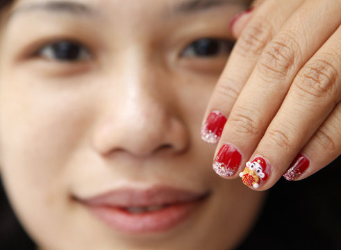 Angel Yang, a manicure artist, displays her creation of a mini figurine of the Chinese God of Wealth pasted on a client's nail before upcoming Chinese Lunar New Year celebrations in Taipei,