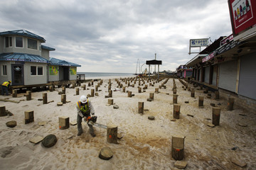 A worker uses a chainsaw to trim new pilings for a replacement boardwalk, almost five months after Superstorm Sandy, in Seaside Heights, New Jersey