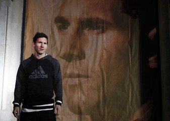 Barcelona's Lionel Messi of Argentina poses next to a picture of himself as he arrives at an event in Barcelona