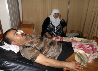 A victim of an attack on a police intelligence headquarters lies on a bed at a hospital in Kirkuk