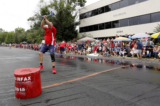 A member of the Indianapolis team drives his axe into a block of wood during the hose cart competition of the Firefighter Muster event at the World Fire and Police Games in Fairfax, Virginia
