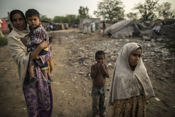 Woman carries her son as they watch children playing on a swing at a slum on the outskirts of Islamabad