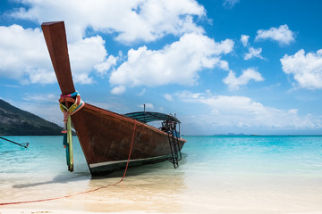 View of a wooden, long tail boat in the foreground on a beach in
