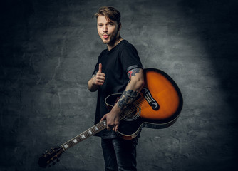 Studio portrait of stylish hipster male holds blues and jazz acoustic guitar.