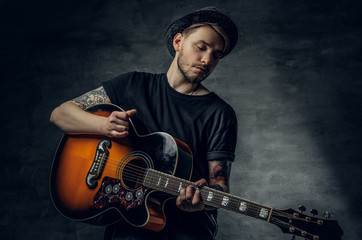 Handsome young acoustic guitar blues player with tattoos on arms.