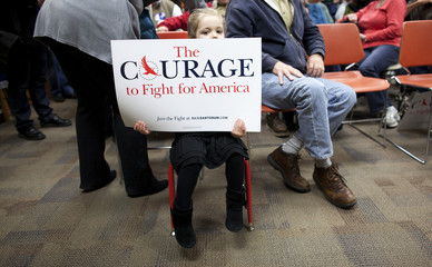 A girl holds up a sign in support of Republican presidential candidate Santorum after he spoke to supporters in Indianola