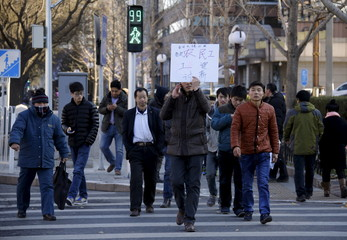 Tian Honglei, a migrant worker from Henan province, holds a placard as he marches with his fellow workers along a main street to protest against a construction site and demand their salaries in central Beijing