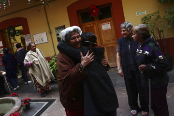 A former sex worker embraces a volunteer during a Three Kings Day celebration at Casa Xochiquetzal, a shelter for female sex workers, in Mexico City