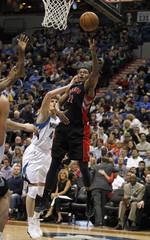 Toronto Raptors forward Rudy Gay shoots around Minnesota Timberwolves' Andrei Kirilenko during their NBA game in Minneapolis