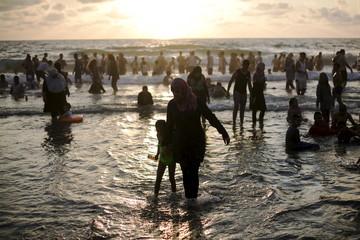 Muslim women watch people in water of Mediterranean in Tel Aviv during Eid al-Fitr