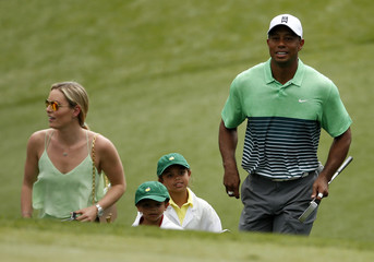 U.S. golfer Woods walks up to the green with his children Sam and Charlie and his girlfiend Vonn during the Par 3 event held ahead of the 2015 Masters at Augusta National Golf Course in Augusta
