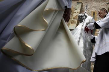 Priests stand in front of a church during an unveiling ceremony of a statue of the late Pope John Paul II in Sarajevo