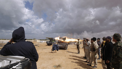 Anti-Gaddafi fighters fire a rocket during clashes with pro-Gaddafi forces at the frontline in Sirte