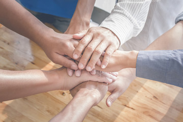 Group of people putting their hands working together on wooden b