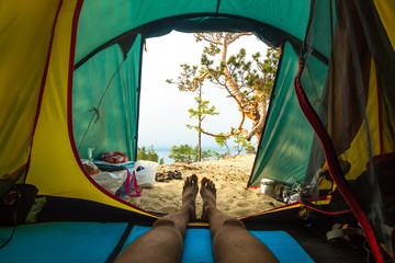 Feet of a man in a tent overlooking the sandy beach and the sea of Baikal