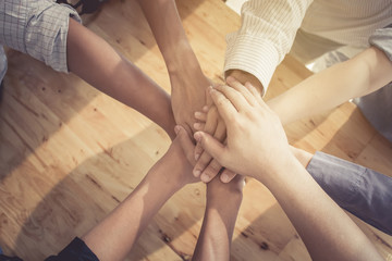Group of people putting their hands working together on wooden background in office. group support teamwork cooperation concept.
