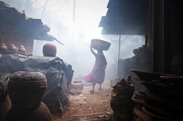 A woman potter carries earthen pots through traditional pottery kilns in Dharavi, one of Asia's largest slums in Mumbai