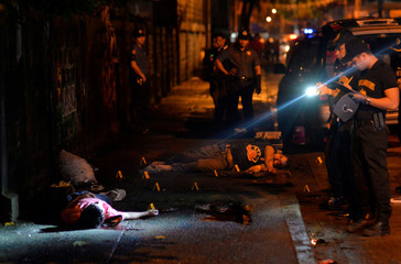 "Police investigators inspect the bodies of two men lying on a sidewalk, who police said, were killed after a drug ""Shabu"" (Metamphetamine Chloride) buy-bust operation in Quezon city, Metro Manila"