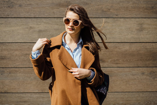 Autumn fashion image of young woman having fun in sunny day in brown coat on the background of wooden wall