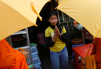 A girl prays as she offers some food to Buddhist monks along a street in Phnom Penh