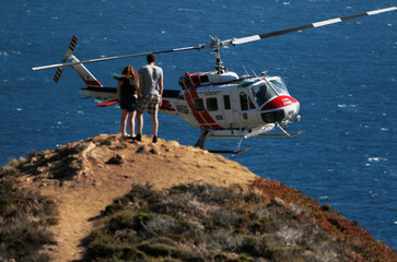A Cal Fire helicopter flies past hikers while picking up water from the Pacific Ocean during the Soberanes Fire north of Big Sur