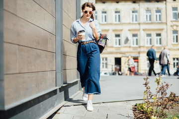 beautiful caucasian girl in sunglasses holding disposable cup and walking along wooden wall on the street the wind in your hair sun street fashion clothing. Full body portrait