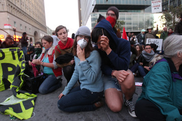 """""""Occupy Wall Street"""" demonstrators sit at an intersection near Oakland City Hall"""