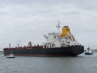 Products tanker ship maneuvering in the harbor with blue tugboat on stern. Horizontal  three-quarter stern view