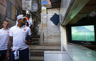 Netherlands' national soccer team player Lens observes a television displaying the 2014 World Cup match between Argentina and Switzerland during a visit to the Santa Marta slum in Rio de Janeiro