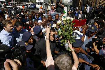 A fan attempts to hand over flowers as South African Olympic and Paralympic sprinter Pistorius arrives for his sentencing at the North Gauteng High Court in Pretoria