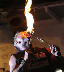 A fire eating performance artist blows fire from his mouth at a bar in Murrells Inlet