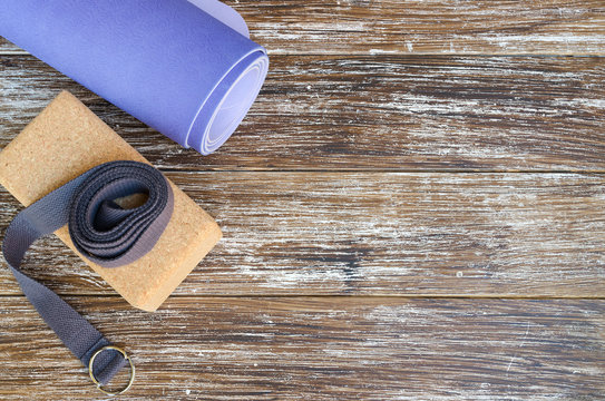 Accessories or props for yoga, pilates or fitness. Exercise lilac mat, two cork blocks and grey strap on wooden background.Copy space.