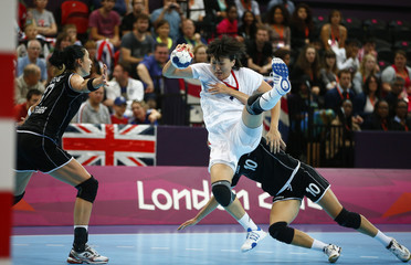 Russia's Liudmila Bodnieva is pulled to the ground by Montenegro's Andela Bulatovic in their women's handball Preliminaries Group A match at the Copper Box venue during the London 2012 Olympic Games