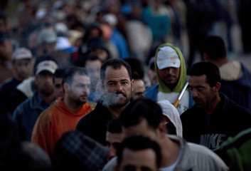 Palestinian labourers wait to cross into Israel at dawn at Hashmonaim checkpoint west of Ramallah