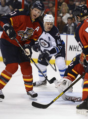 Winnipeg Jets' Jokinen is defended by Florida Panthers' Campbell, Theodore and Goc during their NHL hockey game in Sunrise