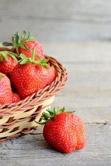 Ripe bright red strawberries. Garden juicy strawberries in a wicker basket and on vintage wooden background. Vertical photo. Closeup