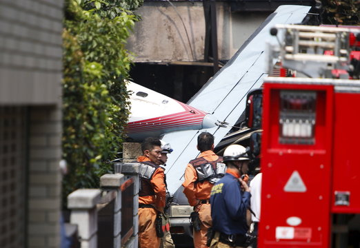 The tail section of a crashed light plane is seen after the plane went down in a residential area and burst into flames, in Chofu, outskirt of Tokyo