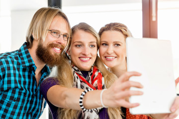 Group of office workers doing selfie indoors