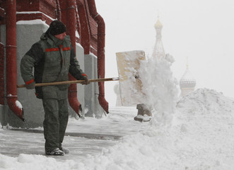 A worker removes snow near Red Square, with St. Basil's Cathedral seen in the background, during heavy snowfall in central Moscow