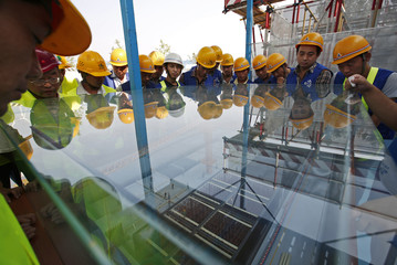 Participants look at a scale model of a construction site as they listen to a lecture at an experience centre for construction safety training in Beijing