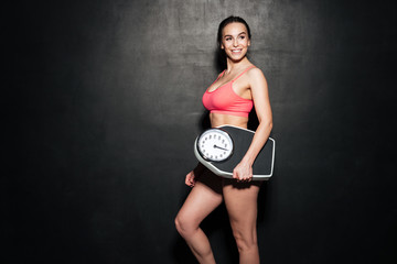 Happy sportswoman holding scales over grey background.