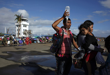 A man holds an IV drip elevated for his daughter during an evacuation at Tacloban airport