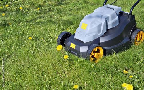 The new electric no name lawn-mower is ready to mow a grass and dandelions