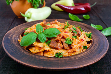 Pasta farfalle with chicken, tomato sauce and basil in a clay bowl on dark wooden background.