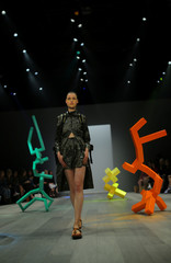 A model for independent fashion label Pageant walks among geometric sculptures during a runway show at Fashion Week Australia in Sydney