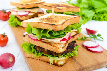 Multilayered sandwiches with a juicy cutlet, cheese, radish, cucumber, lettuce, arugula on a cutting board on a white wooden background.