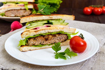Multilayered sandwiches with a juicy cutlet, cheese, radish, cucumber, lettuce, arugula cutting in half on a plate on a dark wooden background. Close up
