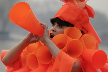 Chinese artist Kong Ning symbolically yells in her costume made of hundreds of orange plastic blowing horns during her art performance raising awareness of the hazardous smog in a historical part of Beijing