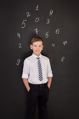 Handsome school boy in googles white shirt tie standing close to school desk with numbers above around the head.