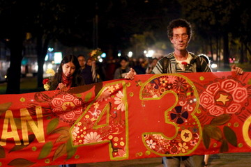 People hold a banner during a demonstration to mark the first anniversary of the disappearance of the students from Mexico's Ayotzinapa College Raul Isidro Burgos, in Guatemala City